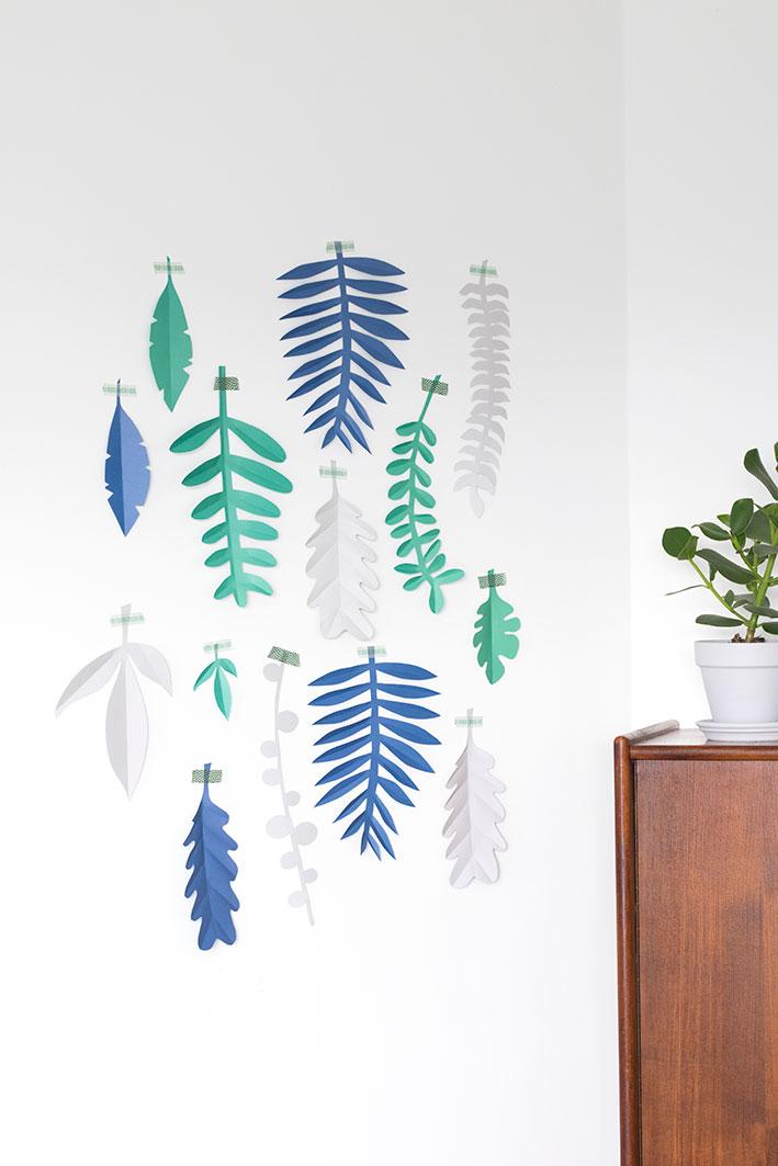 bladeren van papier aan de muur